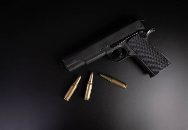 Hand gun with bullets on black background