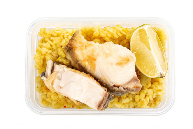 Healthy lunch box with fish, porridge and lime slices