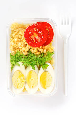 Healthy food concept: lunch box filled with bulgur, vegetables, boiled egg and parsley, top view