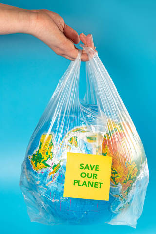 Save our planet inscription on globe in plastic bag
