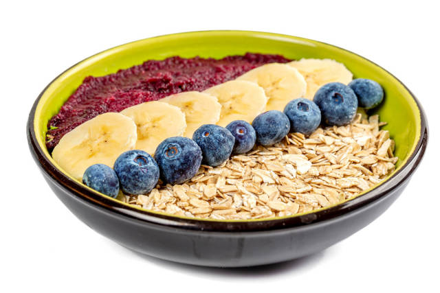Breakfast oatmeal bowl with fresh fruit and plum puree