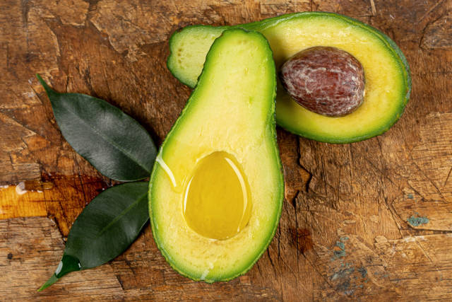 Fresh halves of ripe avocado with oil and leaves