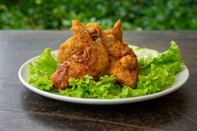 Close Up Food Photo of Fried Chicken Wings with Spicy Tomato Sauce and Lettuce on a White Ceramic Plate