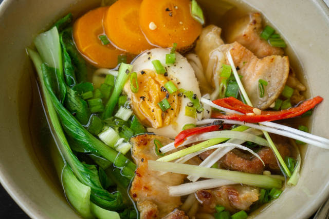 Close Up Food Photo of Ramen Soup with Fresh Vegetables, Egg, Pork and Chili in a Ceramic Bowl