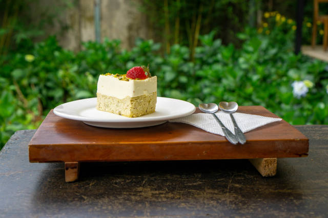 Food Photo of Piece of Cheese Cake with Strawberry and Pistachio on a Wooden Tray with Heart Shaped Spoons and Napkin