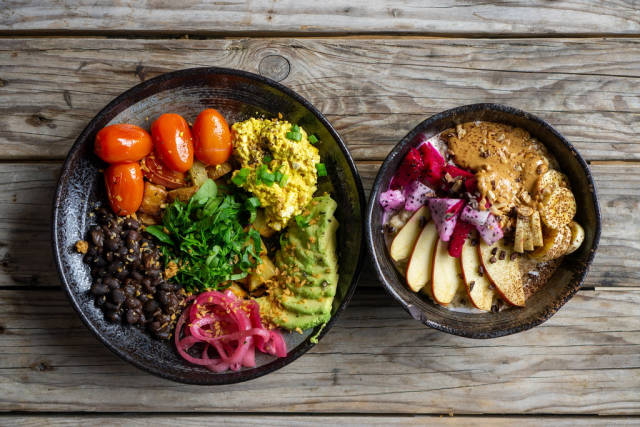 Top View Food Photo of Healthy Breakfast Porridge with Fresh Fruits and Peanut Butter and a Healthy Vegan Lunch with Black Beans, Avocado, Baked Potatoes and Cherry Tomatoes on a Wooden Table