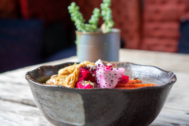 Close Up Food Photo of Red and White Dragon Fruit Cubes in a Healthy Breakfast Bowl with Oatmeal, Peanut Butter, Nuts and Apple with a Table Plant in the Background