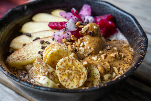 Close Up Food Photo of Healthy Breakfast Bowl with Oatmeal, Cinnamon, Apple, Banana, Dragon Fruit, Chocolate Cubes, Peanuts and Peanut Butter in a Black Ceramic Bowl