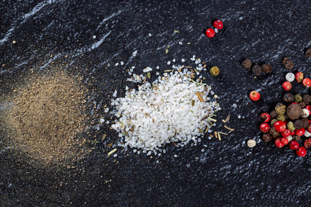 A mixture of peppers, ground black pepper and sea salt on a black background