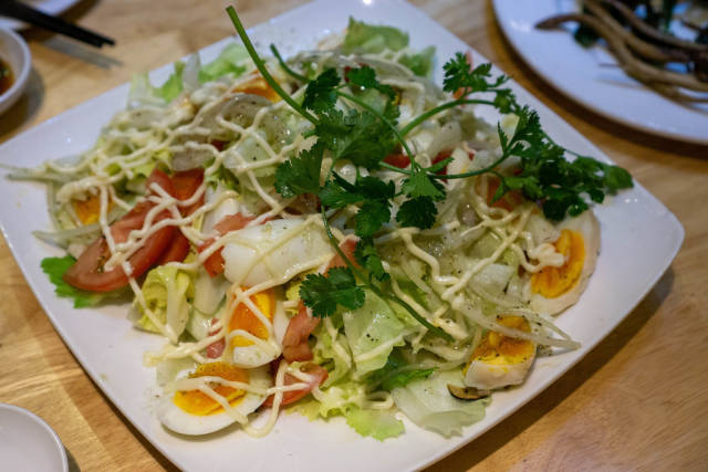 Food Photo of Mixed Salad with Boiled Eggs, Tomatoes, Onions, Parsley and Mayonnaise on a Plate in a Restaurant