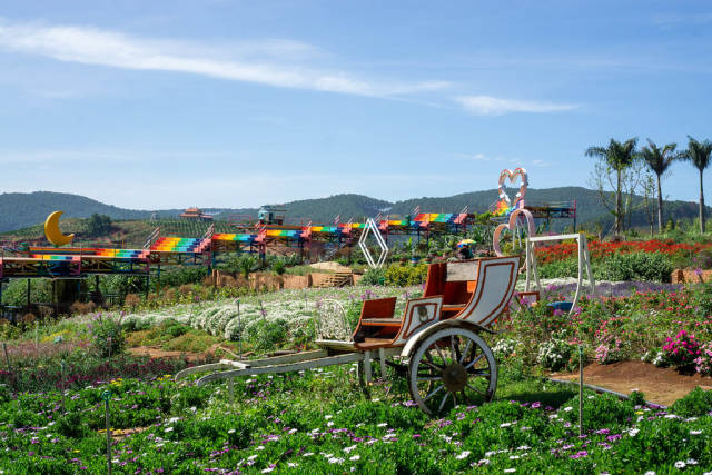 Carriage and Swing in a Flower Garden with Colored Stairs in the Background at Me Linh Coffee Garden in Da Lat, Vietnam