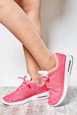 Unrecognizable athletic woman wearing pink sneakers before fitness workout