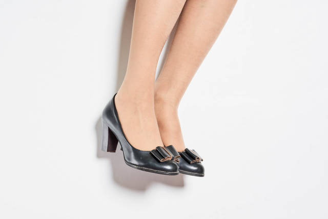 Partial view of woman in black shoes with a steady average heel for daily wear