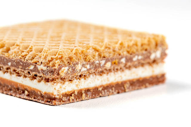 Waffle with chocolate and nuts on a white background close-up