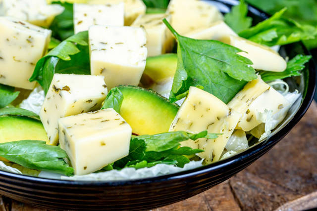 Close-up salad with spicy cheese, avocado and parsley leaves