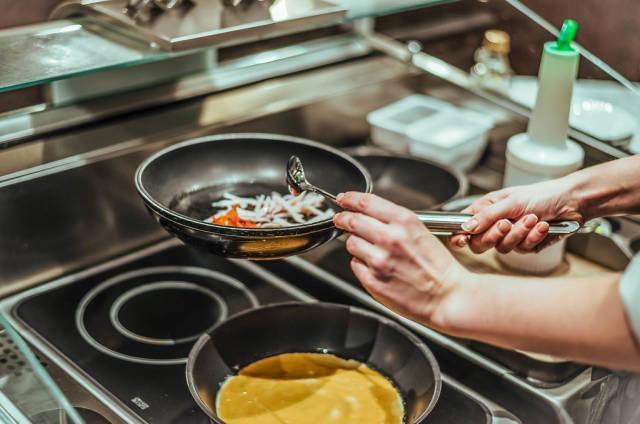 Koch bereitet Omelette mit Schinken zu