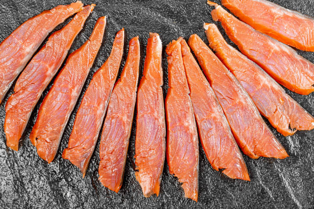 Top view sliced pieces of smoked red fish fillet