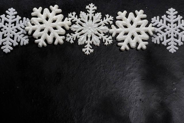 White snowflakes on a black background. Free space