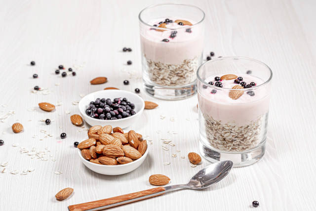 Breakfast concept. Oatmeal with almonds, yogurt and black elderberry