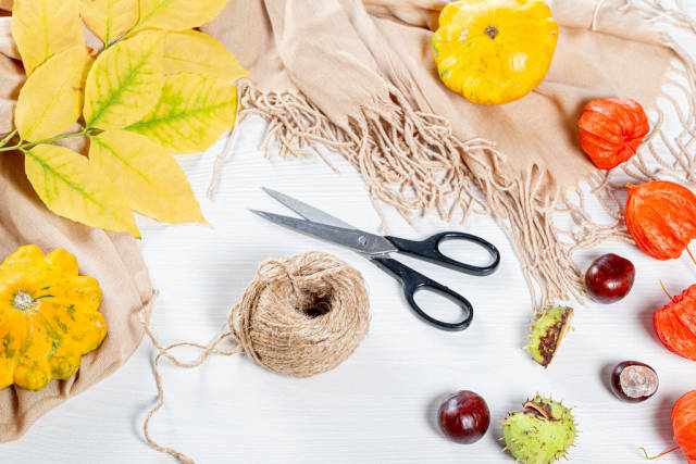 Colorful autumn background with leaves, physalis, scarf, scissors and thread. The concept of preparation for the autumn holidays