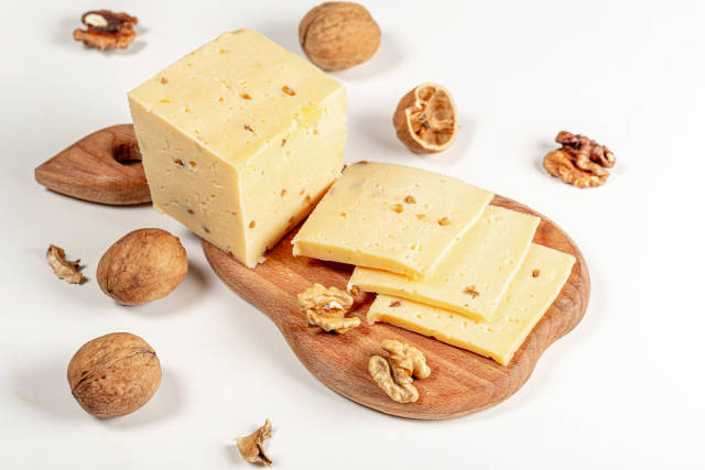 Fresh cheese with walnuts on wooden kitchen Board on white background
