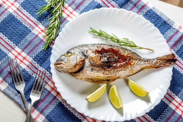 Delicious cooked Dorado fish with slices of lime and a sprig of rosemary