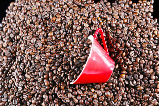 Red cup of coffee over coffee beans background