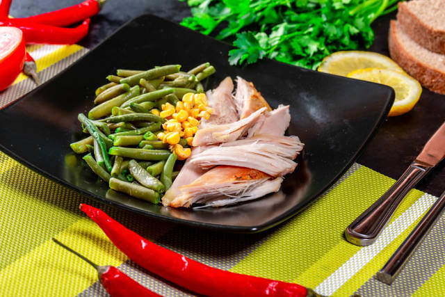 Black plate with healthy food - boiled asparagus, corn and baked chicken breast