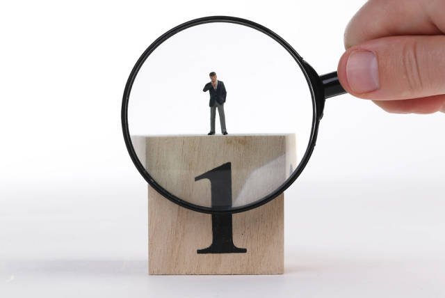 Businessman standing on top of wooden cube with big number 1 and magnifying glass
