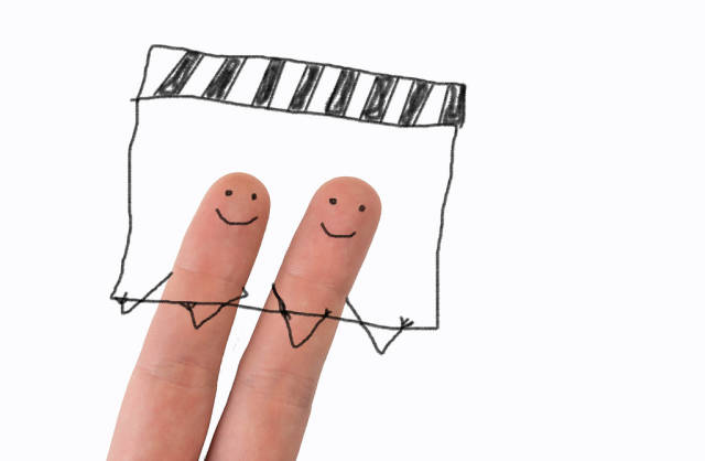 Two painted happy fingers with movie clapper