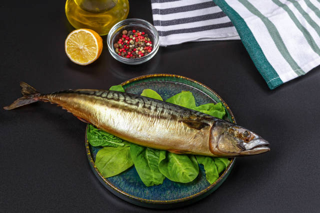 Whole smoked mackerel on a dark background with spices