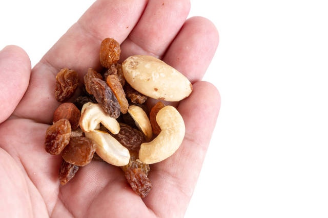 Energy mix with raisins hazelnuts cashew and brazilian nuts in the hand