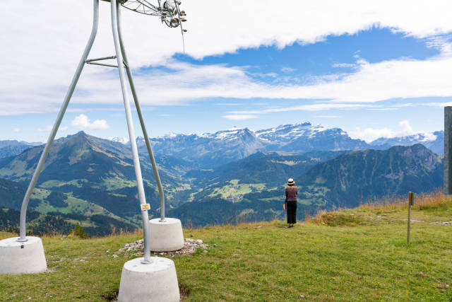 Tourist taking a picture of Swiss Alps at the edge of the world next to weather station