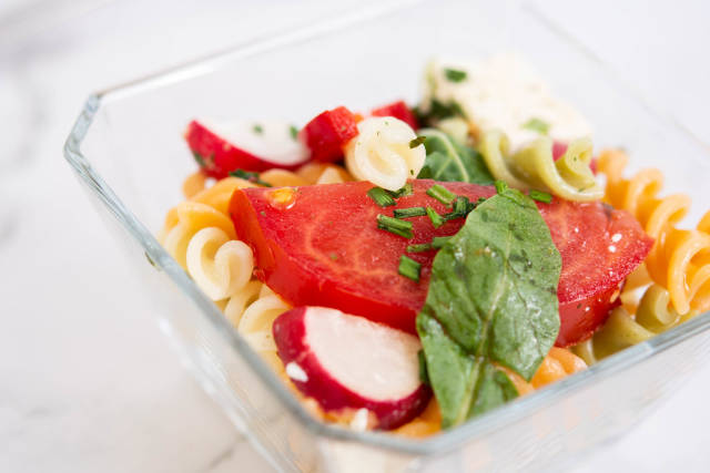 Tomato Radishes Rukola and Cheese salad in the glass bowl