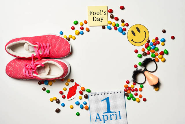 April fools day surprise - shoelaces tied together, calendar, party mask and sweet candies on white background