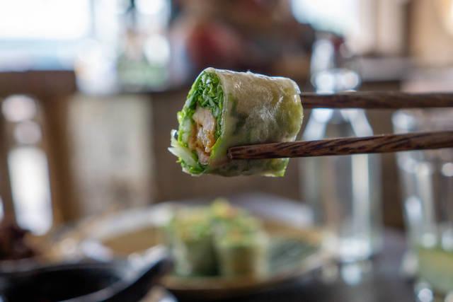 Bokeh Food Photo of Chopsticks holding a Piece of Goi Cuon - Vietnamese Summer Rolls in a Restaurant in Vietnam
