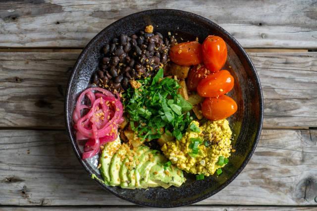 Gesundes Frühstück mit Rührei, Avocado, Kirschtomaten, Bohnen und Bratkartoffeln von oben auf einem Holztisch fotografiert