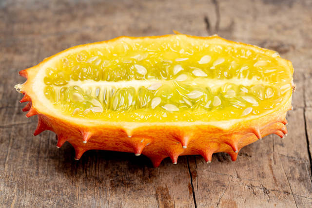 Kiwano fruit half on old wooden background
