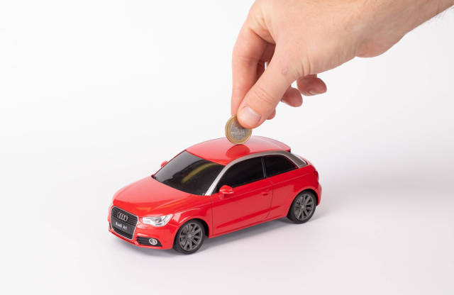 Putting coin into the car on white background
