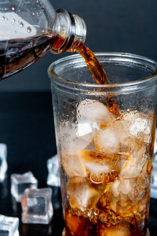 Pepsi is poured from a bottle into a glass with ice