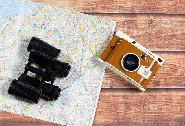 Old vintage camera and binoculars on a old world map