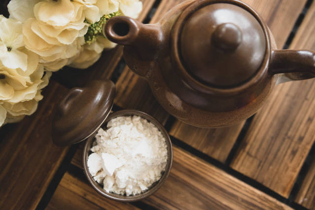 Top view of white powder and teapot on a wooden surface