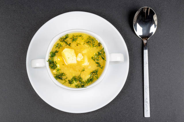 Pea soup with dill greens in a tureen on a black background, top view