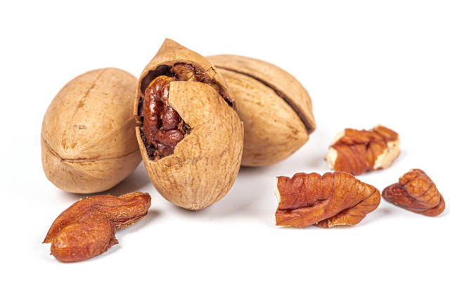 Ripe pecans with shells on a white background