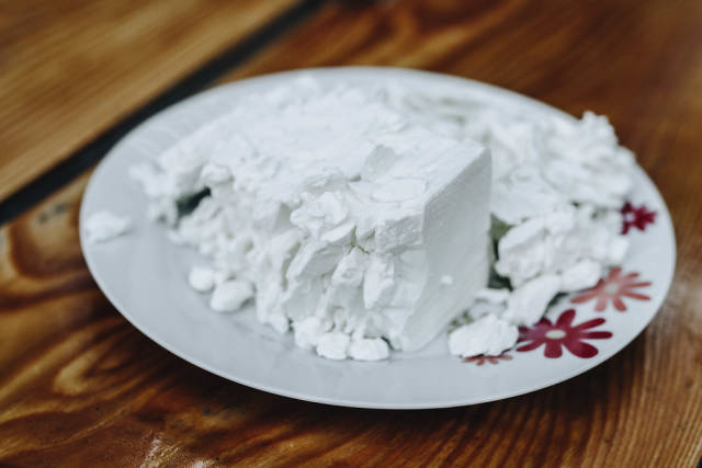 Feta cheese in a white plate on wooden background