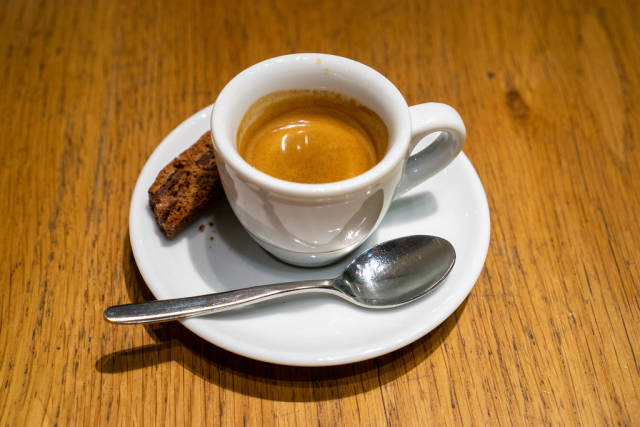 Close Up Photo of Espresso Cup on a Saucer with Spoon and Chocolate Cookie