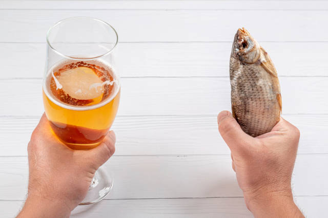 Mens hands with beer and dried fish