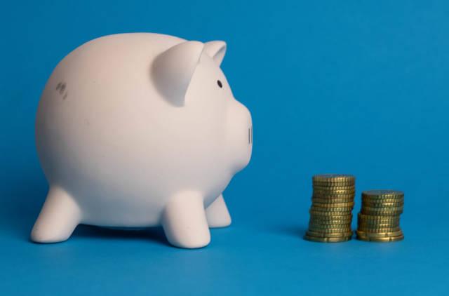 Ein Sparschwein mit Münzen auf hellblauem Hintergrund