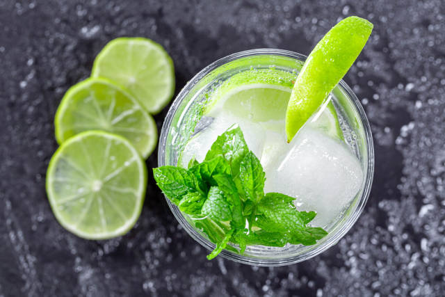 Fresh Mojito cocktail in glass with ice on a black background. Top view