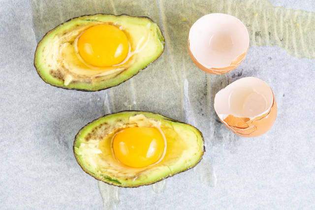 Sliced Avocado with raw Eggs ready for baking